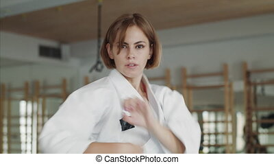 Young woman practising karate indoors in gym.