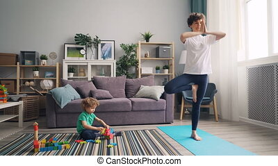 Young woman practising yoga at home while calm child playing with toys on floor