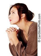 Young woman praying and looking up.