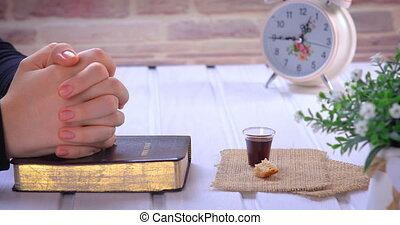 Young woman praying and taking communion - the wine and the bread symbols of Jesus Christ blood and body with Holy Bible. Closeup dolly shot