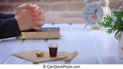 Young woman praying and taking communion - the wine and the bread symbols of Jesus Christ blood and body with Holy Bible. Focus on glass. Closeup dolly shot