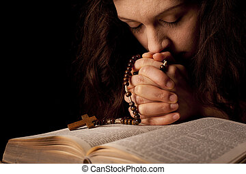 Young woman praying on holy bible with rosary