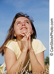 Young woman prays in nature