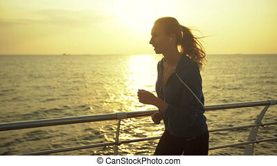 Young woman preferring healthy mode of living, running near the sea.
