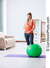 Young woman preparing for birth exercising at home