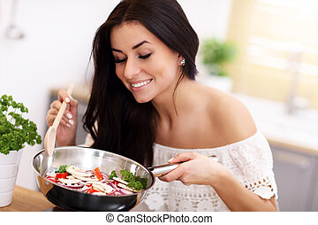Young woman preparing fried vegetables in kitchen
