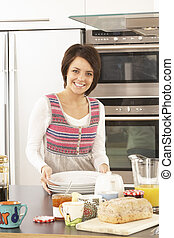 Young Woman Preparing Meal In Modern Kitchen