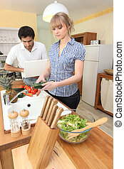 Young woman preparing salad in kitchen