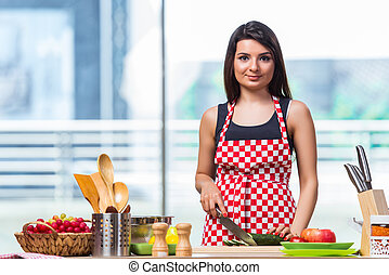 Young woman preparing salad in the kitchen