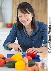 young woman preparing vegetables in a domestic setting