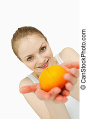 Young woman presenting a tangerine against white background