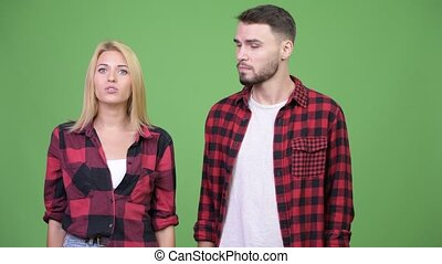 Young woman presenting young man together - Studio shot of...