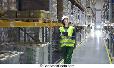 Young woman professional using tablet during working day at factory warehouse.