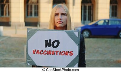 Young woman protesting against vaccination. She walking down the street