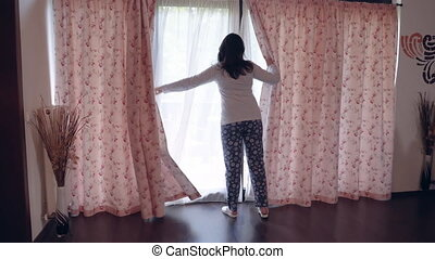 Young woman pulling the curtains in the morning and...