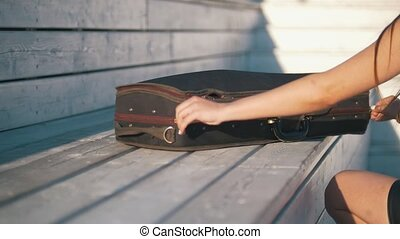 Young woman pulls her violin from the case outdoors at...