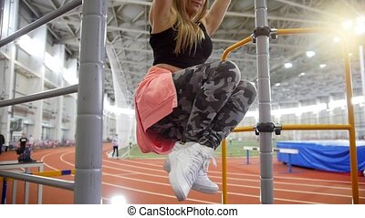 Young woman pulls up on the crossbar in the sports hall....