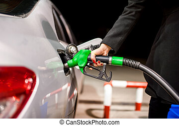 Young woman pumping gas in car at petrol station