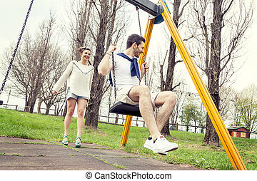 young woman pushes her boyfriend on the swing