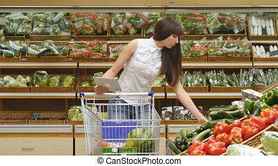 Young woman pushing cart along the grocery aisles in the supermarket and using tablet pc to check shopping list. Girl choosing fresh vegetables in grocery and putting them in the shopping trolley..