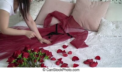 Young woman put on bed red lingerie and roses