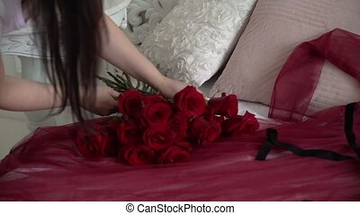 Young woman put on bed tray with jewelry ring and red roses