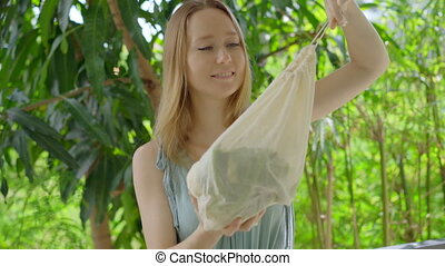 Young woman puts a cauliflower in a reusable bag. Concept of...