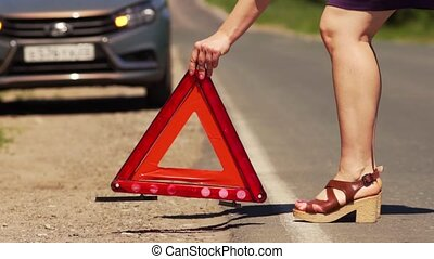 Woman Puts A Red Emergency Stop Sign On The Road