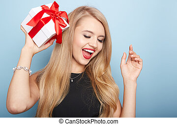 Young woman puts her ear to the present wrapped.