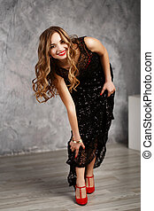 Portrait of a beautiful long-haired young girl in black cocktail dress.