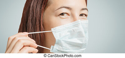 Young woman puts on a medical protective facial mask.