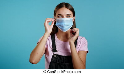 Young woman puts on face medical mask during coronavirus pandemic. Portrait on blue background. Protection with respirator against COVID-19 outbreak. High quality 4k footage