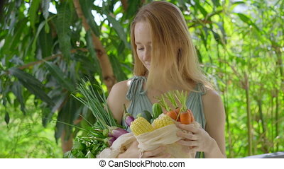 Young woman puts several kinds of vegetables in a reusable ...