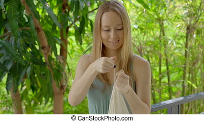 Young woman puts some cherimoya fruits in a reusable bag. ...