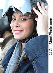Young woman putting a crash helmet on