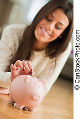 Young Woman Putting Coin In Piggybank