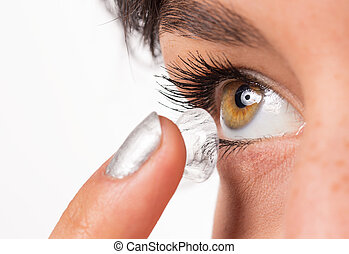 Young woman putting contact lens in her eye.