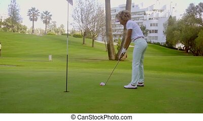 Young woman putting for the hole on a golf course
