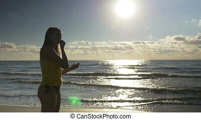 Young woman putting headphones and going for a run on the beach