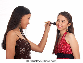 Young woman putting make up on her girlfriend