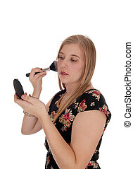 Young woman putting makeup on her face