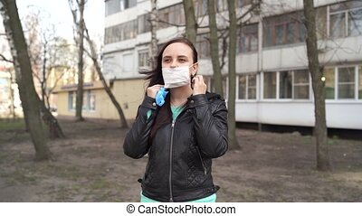 Young woman putting medical mask on her face on street. Close up of female protecting yourself from diseases on walk. Concept of threat of coronavirus epidemic infection