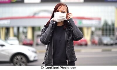 Young woman putting medical mask on her face on street in city. Close up of female protecting yourself from diseases on walk. Concept of threat of coronavirus epidemic infection