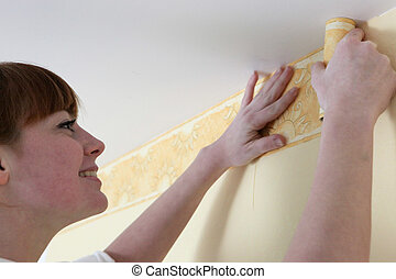young woman putting new wallpapers
