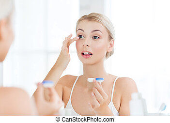 young woman putting on contact lenses at bathroom - beauty,...