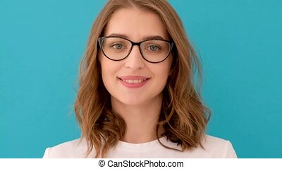 Smart young lady looking at camera and putting on glasses against blue background