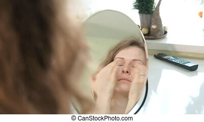 Young woman putting on mascara and looking in hand mirror in...