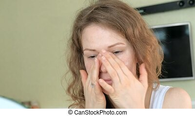 Young woman putting on mascara and looking in hand mirror in bedroom at home
