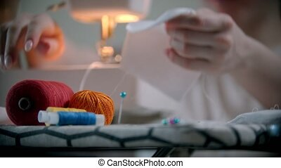 Young woman putting pins in the white cloth before sewing. ...