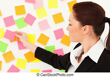 Young woman putting repositionable notes